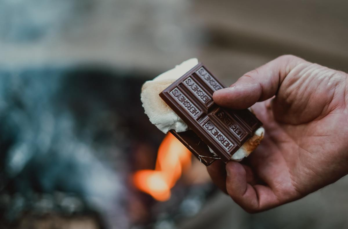 Person holds a s'mores sandwiched with Hershey's bars.