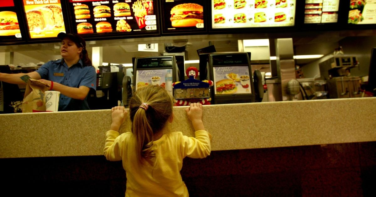 A little girl waits at the counter of a fast food restaurant