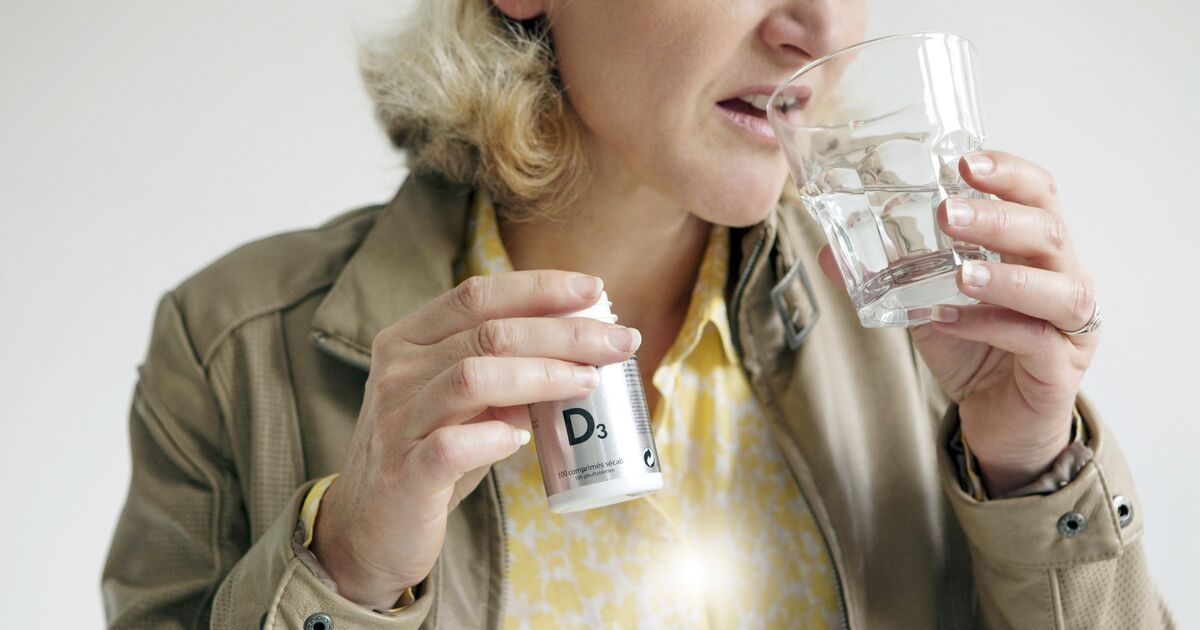 A woman takes a vitamin D supplement