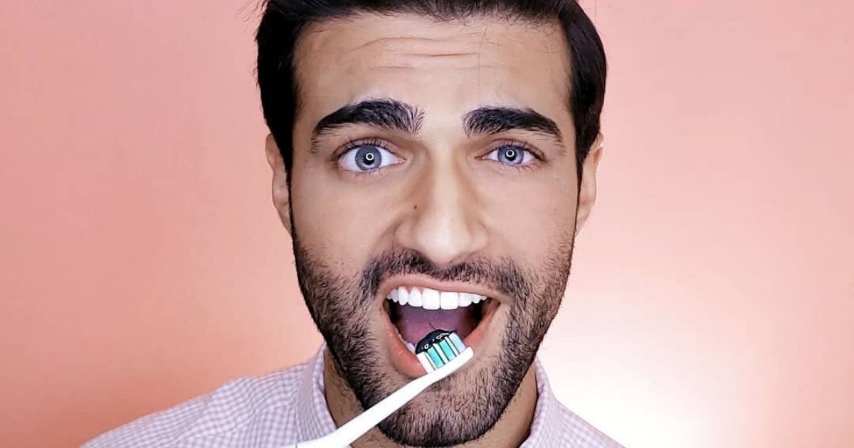 A man about to brush his teeth with black charcoal toothpaste
