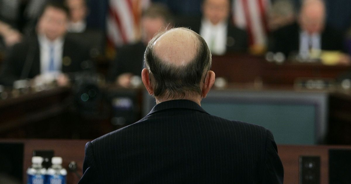 A man stands with his balding head facing the camera