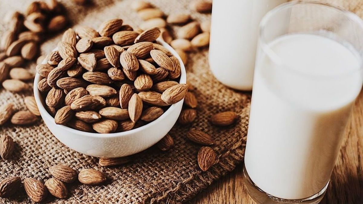 A bowl of almonds sits next to a glass of almond milk