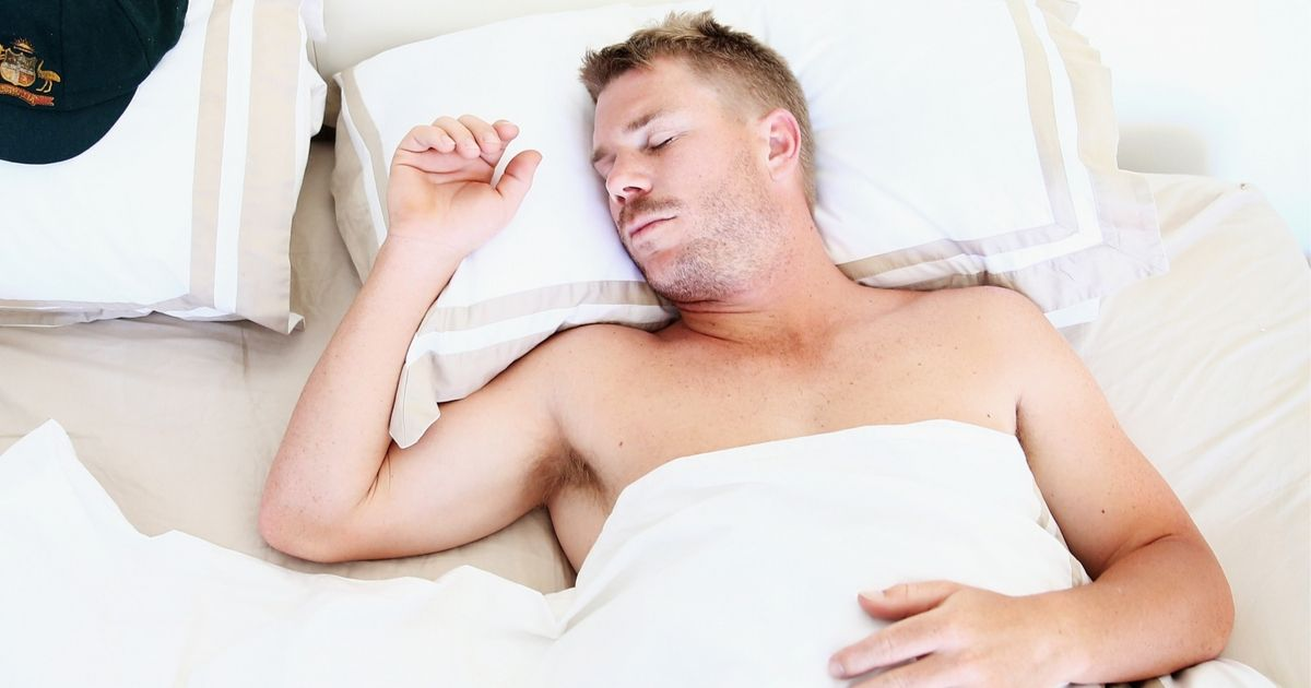 A man asleep in a bed with white sheets