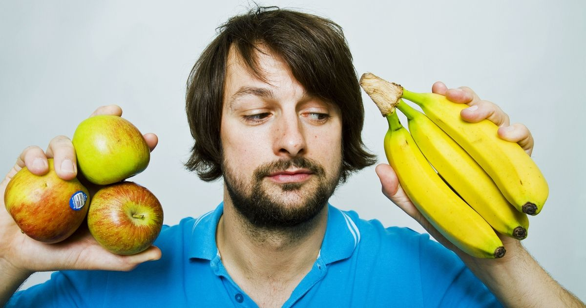 A man holds up three apples in one hand and a bunch of bananas in the other