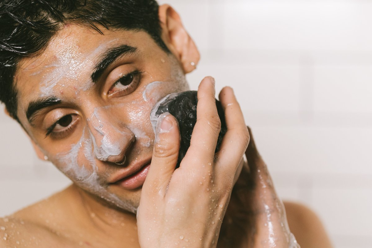 Man washes his face with a charcoal soap bar