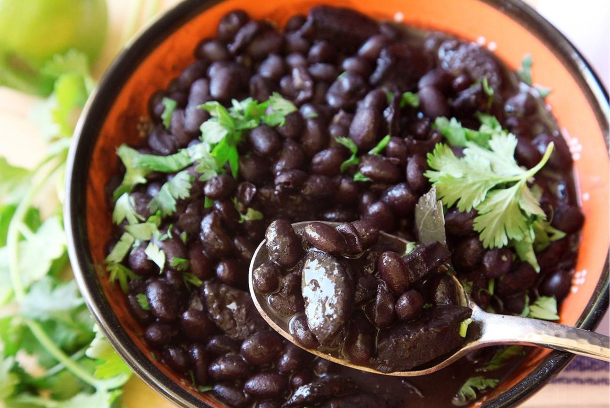 Spoon dips into a black bean dish with cilantro