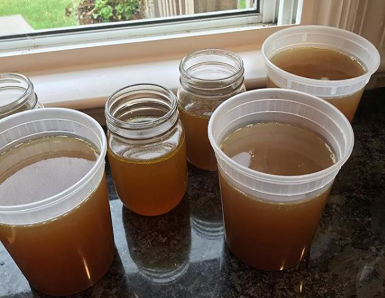 Cups of bone broth sit near the windowsill.