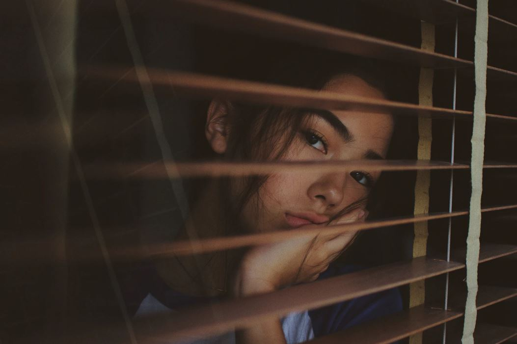 Woman stares out of a window in Bangkok, Thailand