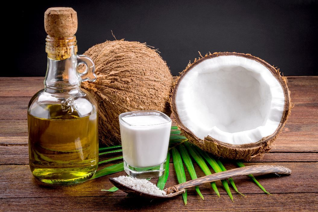 Bottle of liquid coconut oil in front of an open coconut