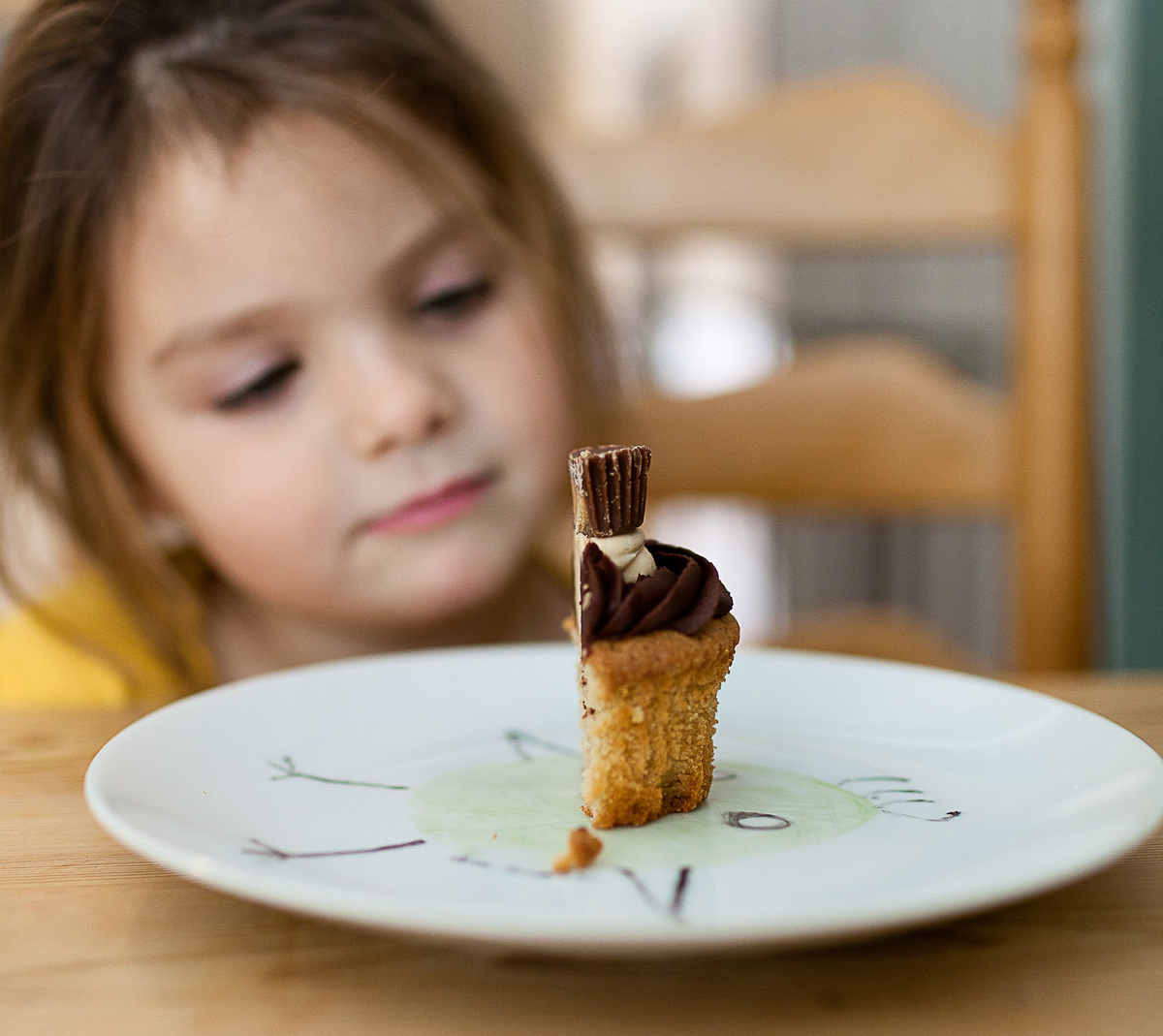 Girl stares at half of a cupcake on a plate.