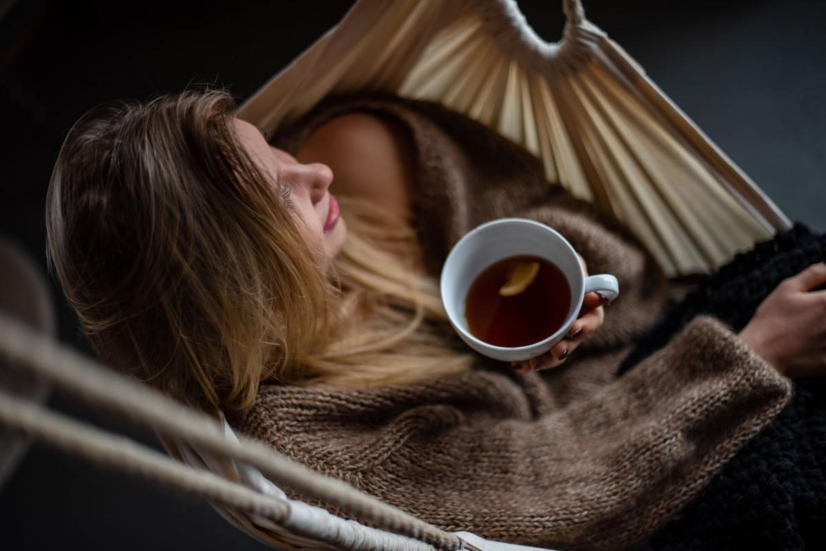 Woman drinks green tea in a hammock
