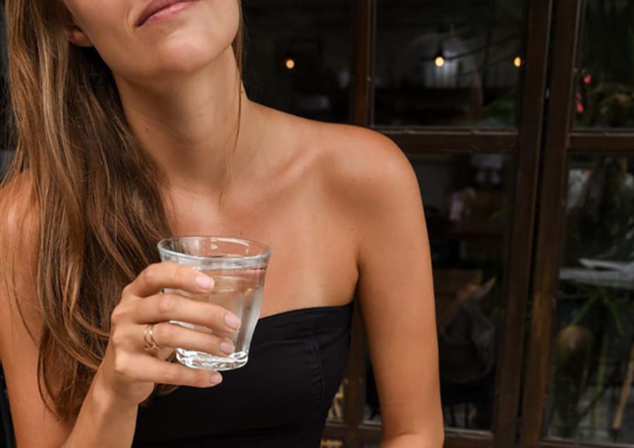 Woman drinks water at a cafe in Bali