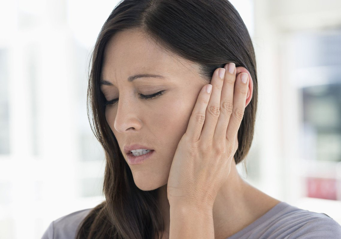 Woman clutches her ear in pain.