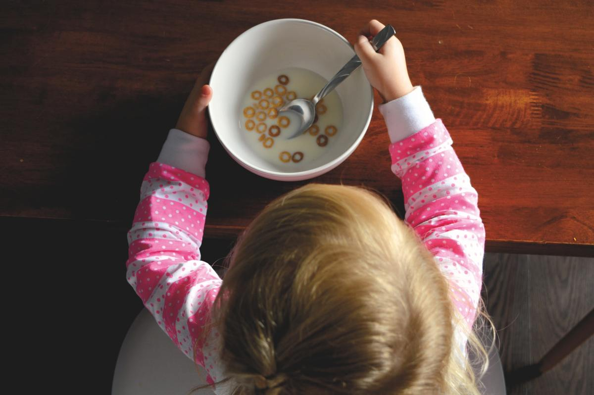 Child eats cheerios cereal for breakfast