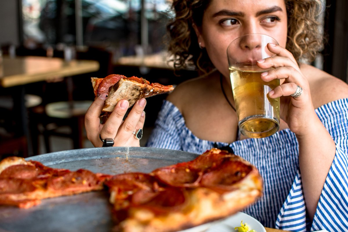 Woman eats pizza at a restaurant and drinks beer