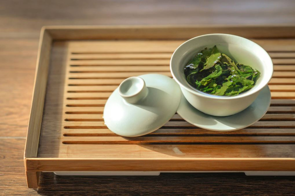 Green tea leaves steep in a tea cup