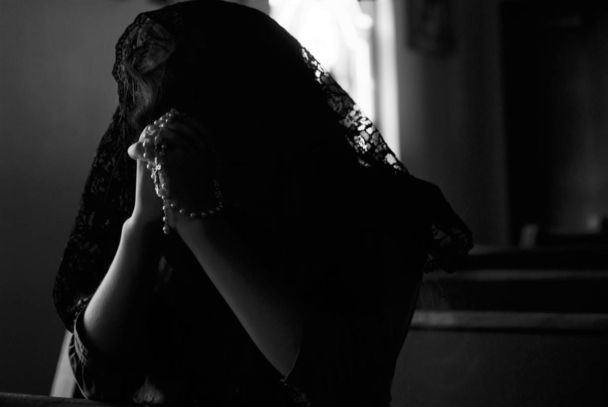 Person in a black veil prays with their rosary