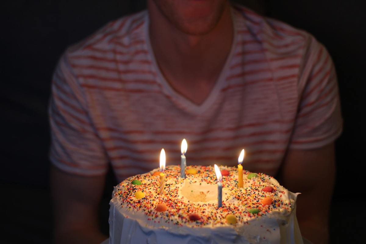 Man holds a lit birthday cake in low light.