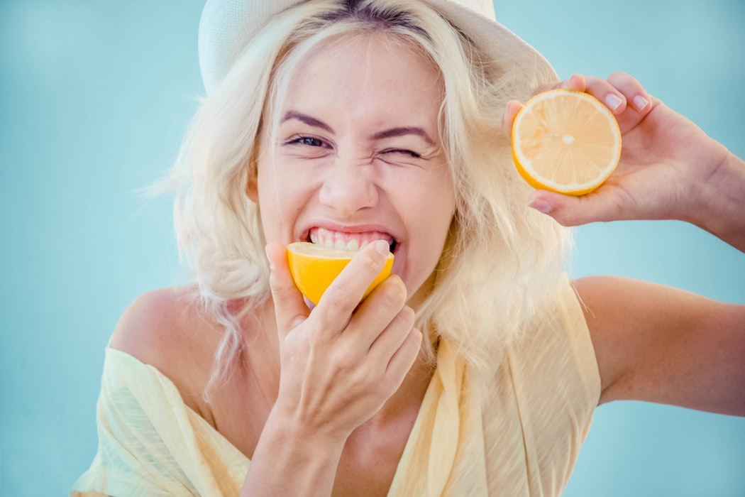 Woman bites one half of lemon and holds the other half up