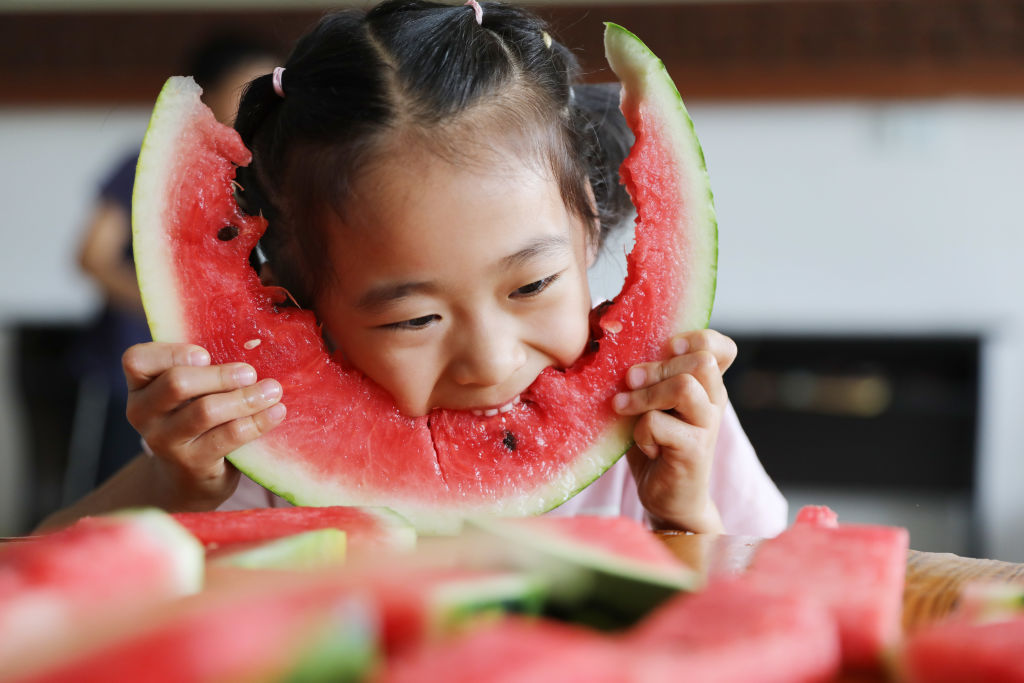 a young girl eating a big piece of watermelon