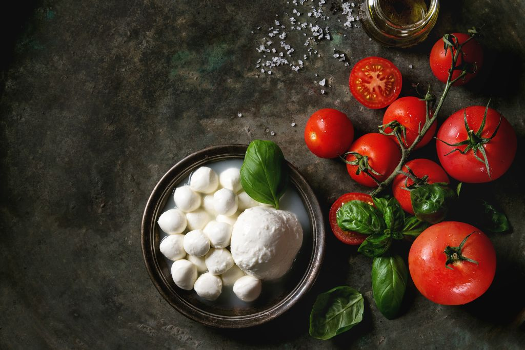 mozzarella balls on a plate with basil and tomatoes