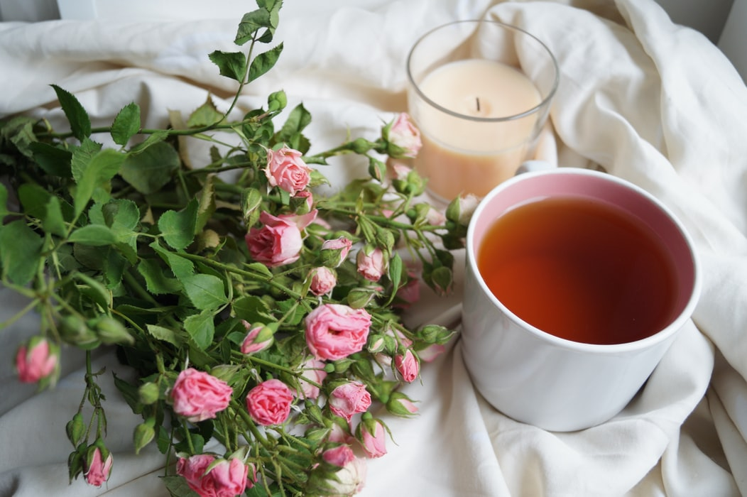 A cup of passionfruit tea sits on a bed next to a candle and flowers.