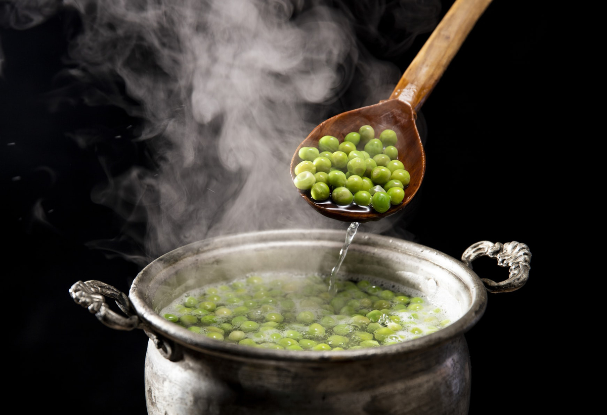 Cooked peas are dished out of a pot with a wooden spoon.