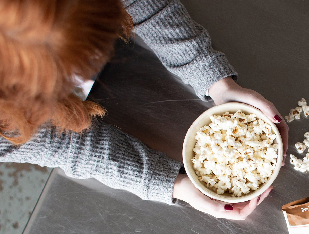 Girl eats popcorn for a snack.