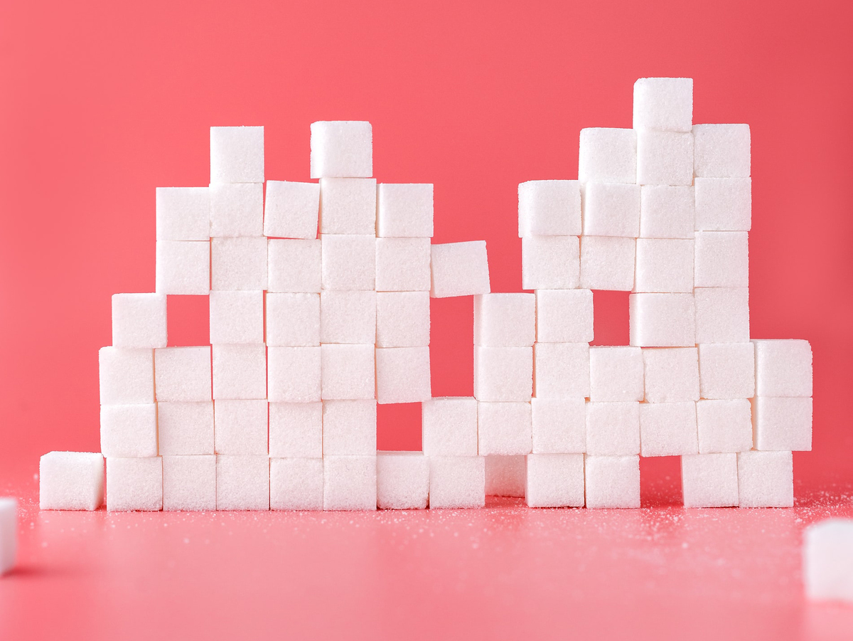 Sugar cubes form a tower against a pink background.