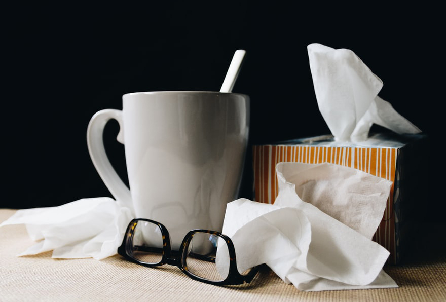 Tissues lay next to glasses and a cup of tea.