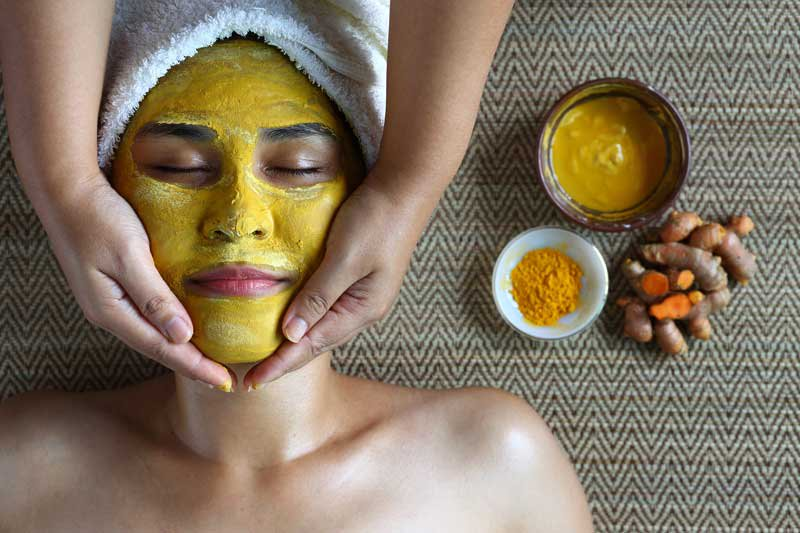 Woman receives a handmade turmeric face mask.