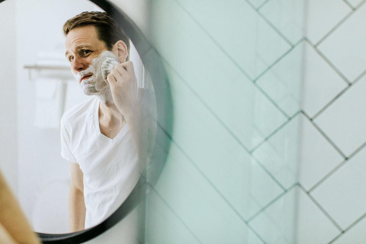 Man applies shaving cream to his face uncomfortably.