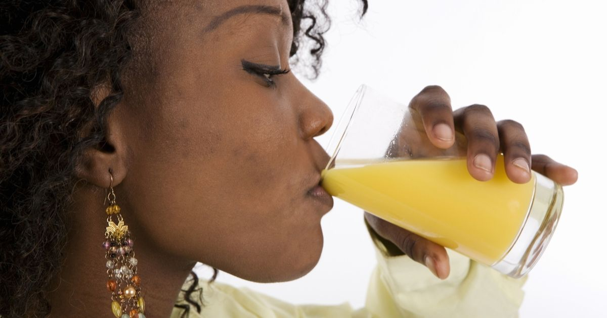 Profile of young woman drinking glass of orange juice