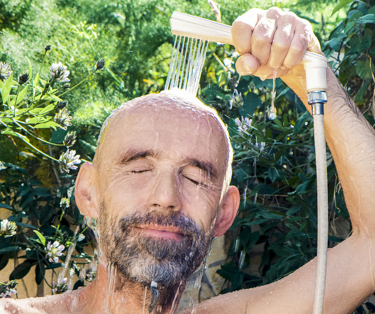 Man sprays water on his head with a shower head.