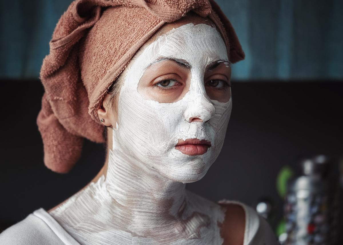 Woman has a white face mask on her face, neck, and chest