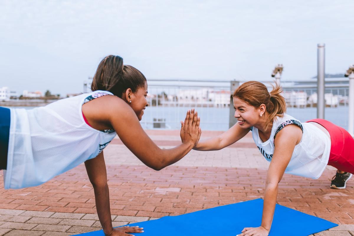 Two women practice yoga outside