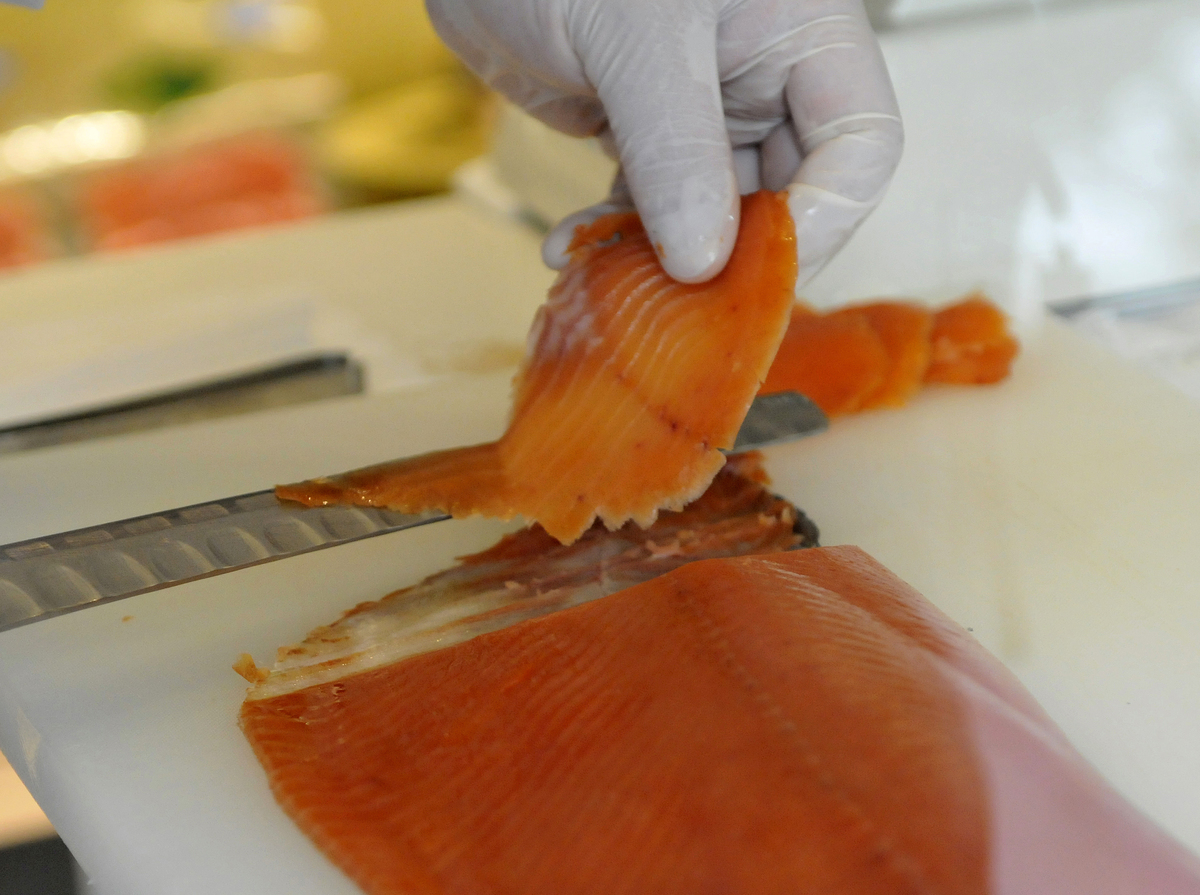 A chef slices raw salmon at a shop in Tokyo.