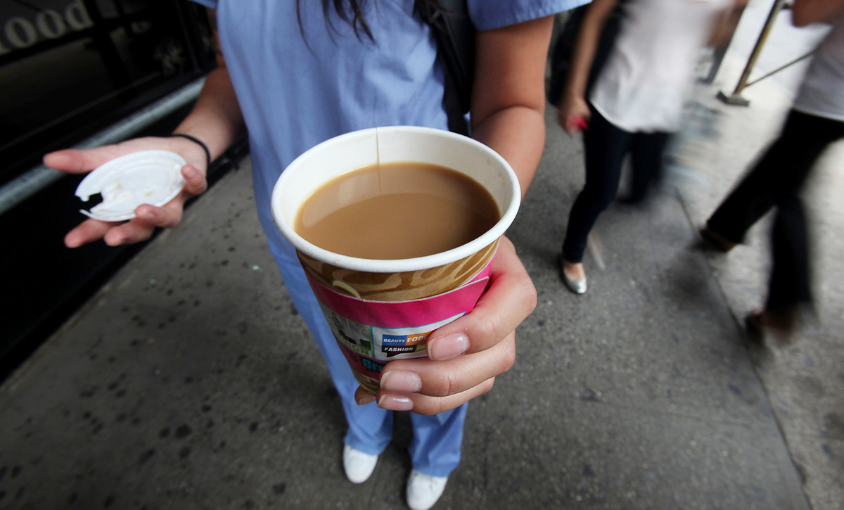 A woman holds a to-go cup of coffee on the street.