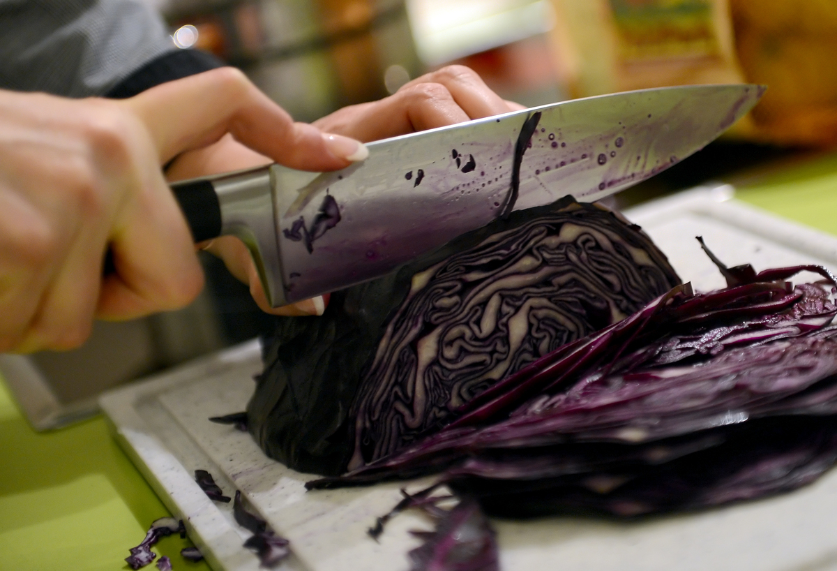 A participant of a cooking class cuts red cabbage for a vegan Christmas dinner.