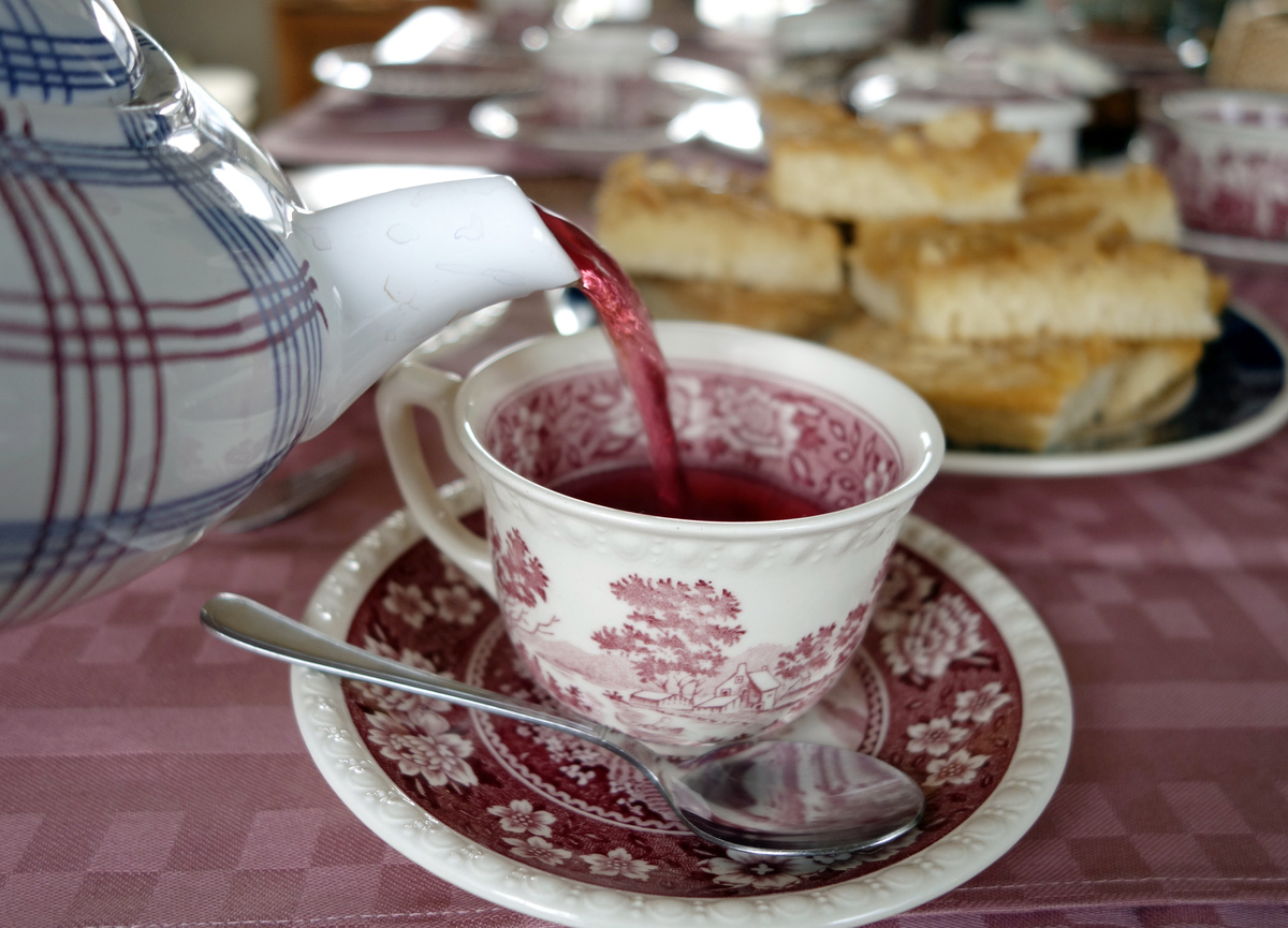 Tea pours out of a tea pot into a porcelain cup on a table.