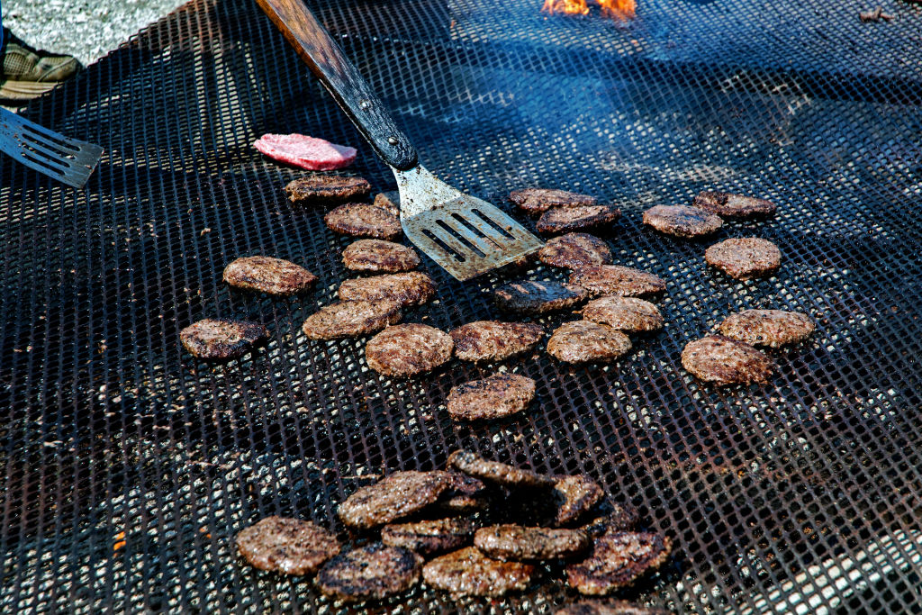 Several patties of beef are grilled at once.