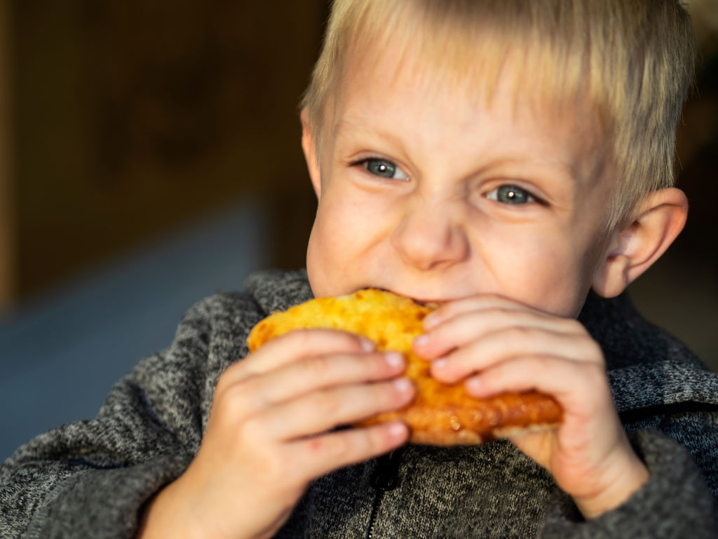 young boy eating bread