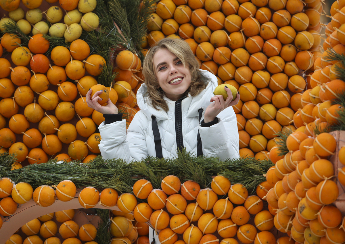 A woman poses for a picture inside a castle made from oranges and lemons.