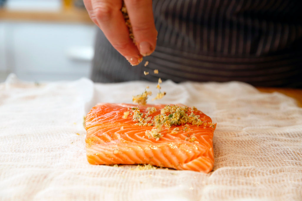 A man sprinkles seasoning over a raw fish fillet.