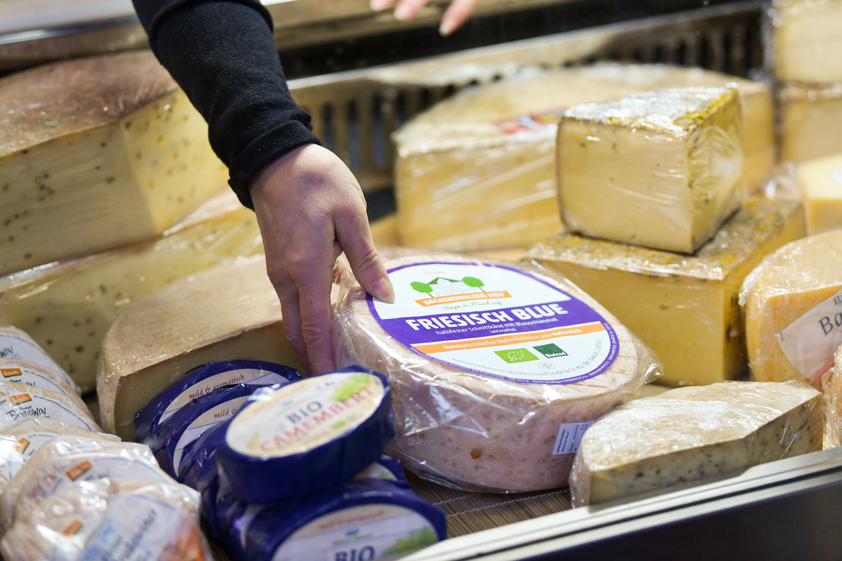 A saleswoman reaches for a cheese wheel.