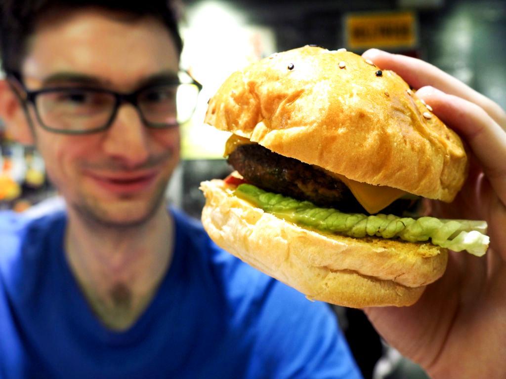 A man holds up a veggie burger.