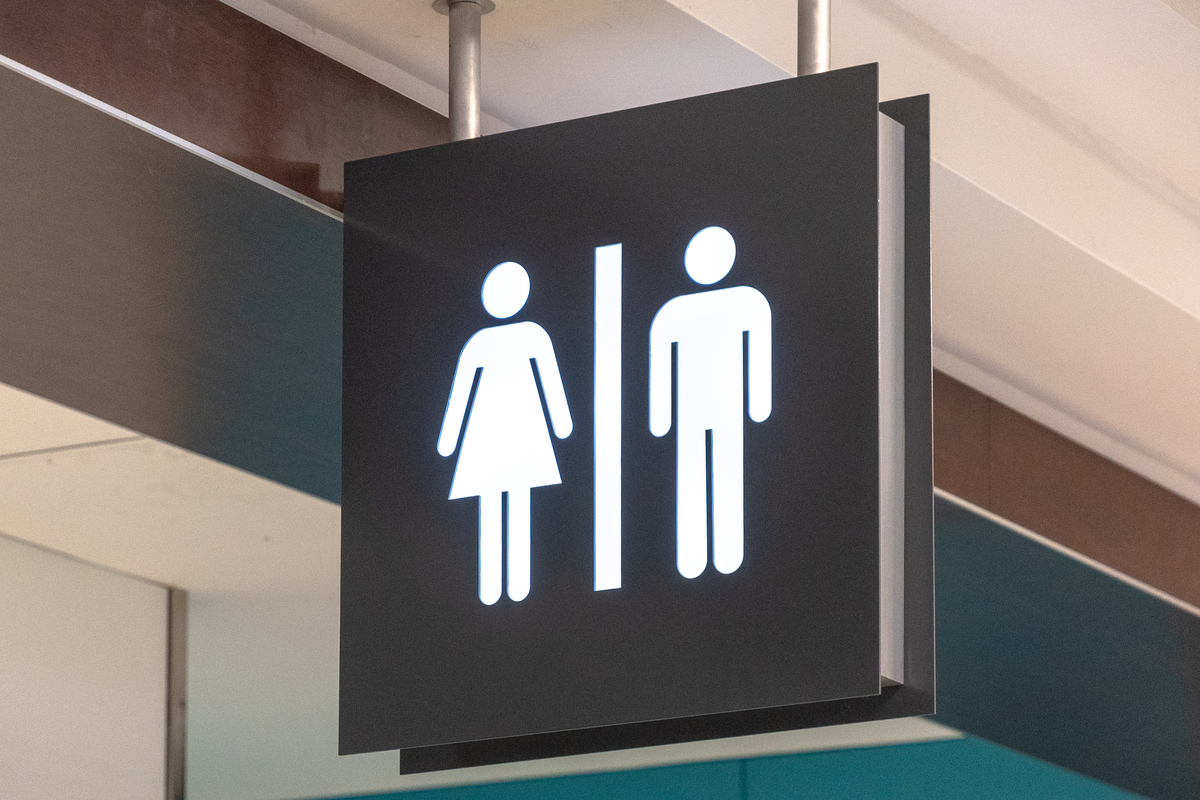 Public washroom or bathroom sign hanging from the ceiling of Pearson International Airport.