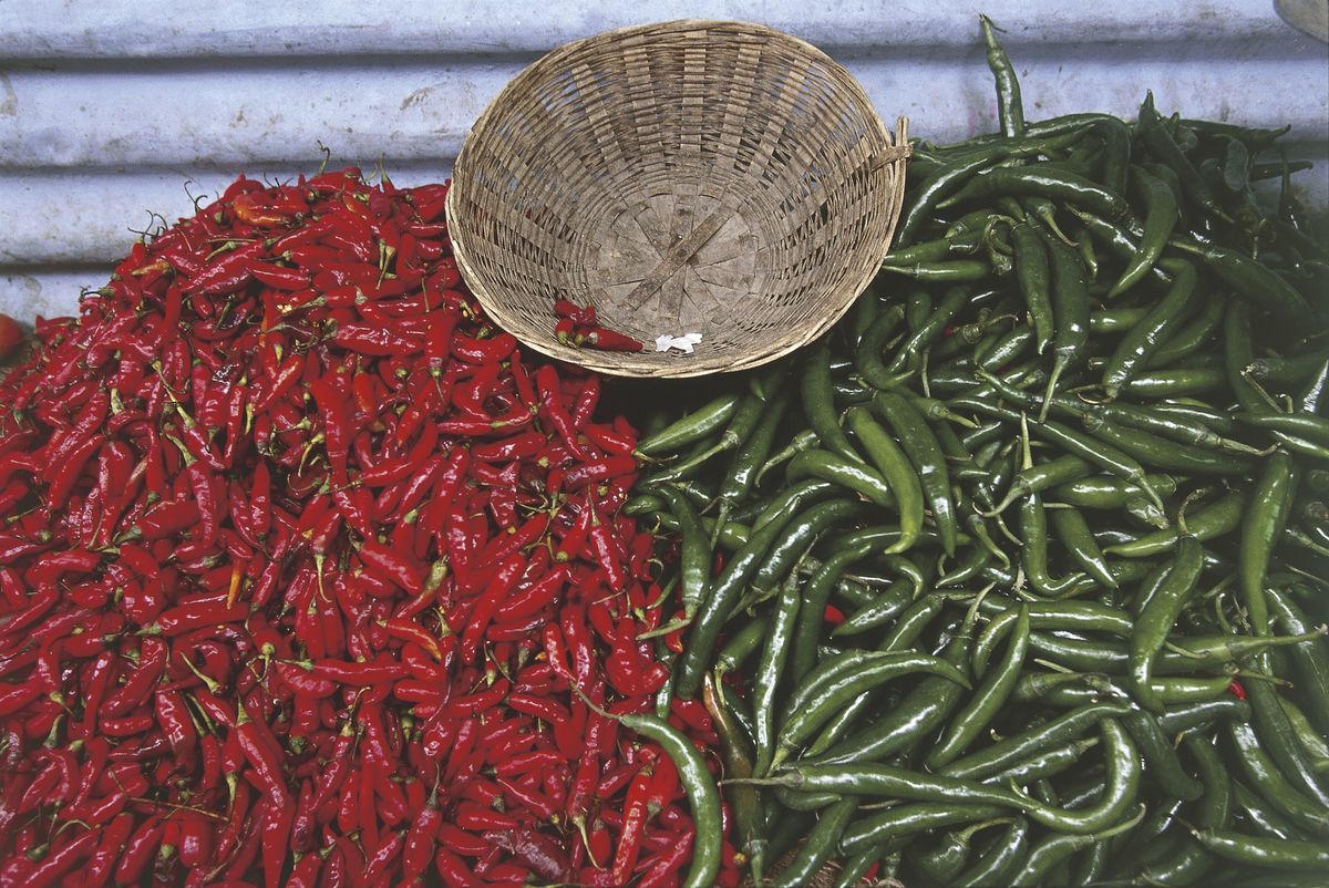 Red and green chili peppers line up near a woven basket.