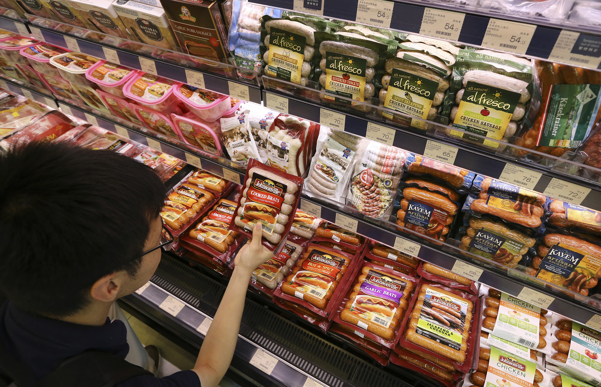 A customer chooses from preserved sausages and hams at a supermarket.