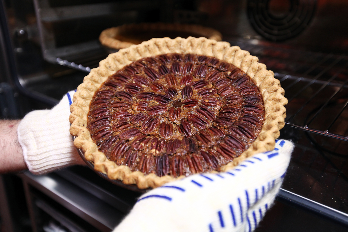 Baker pulls a pecan pie out of an oven.